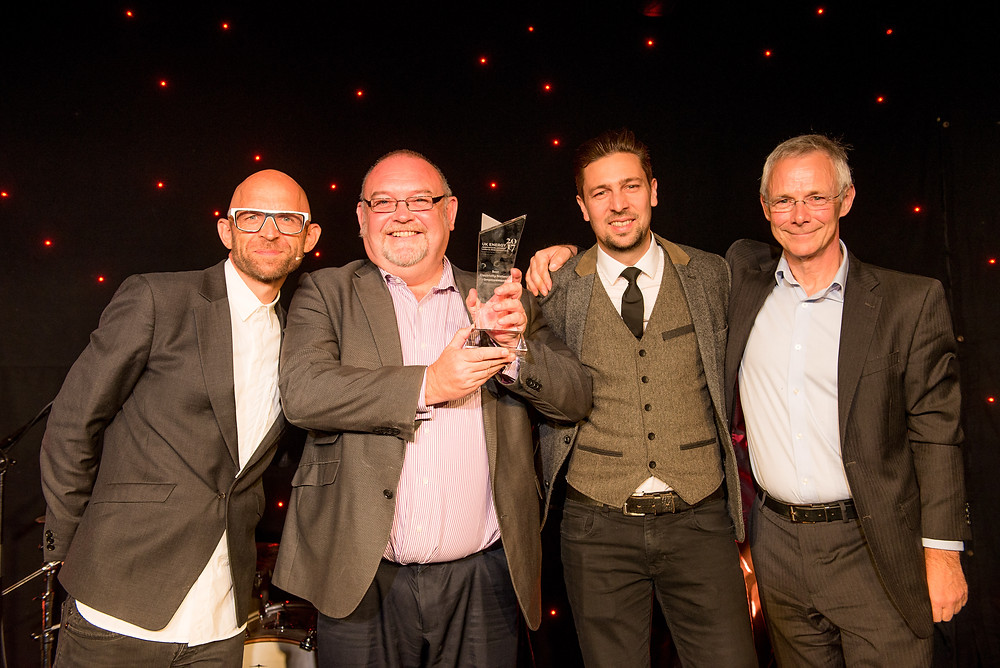 The NM Group team accepting their award at the 2017 UK Energy Innovation Awards from host, Jason Bradbury.