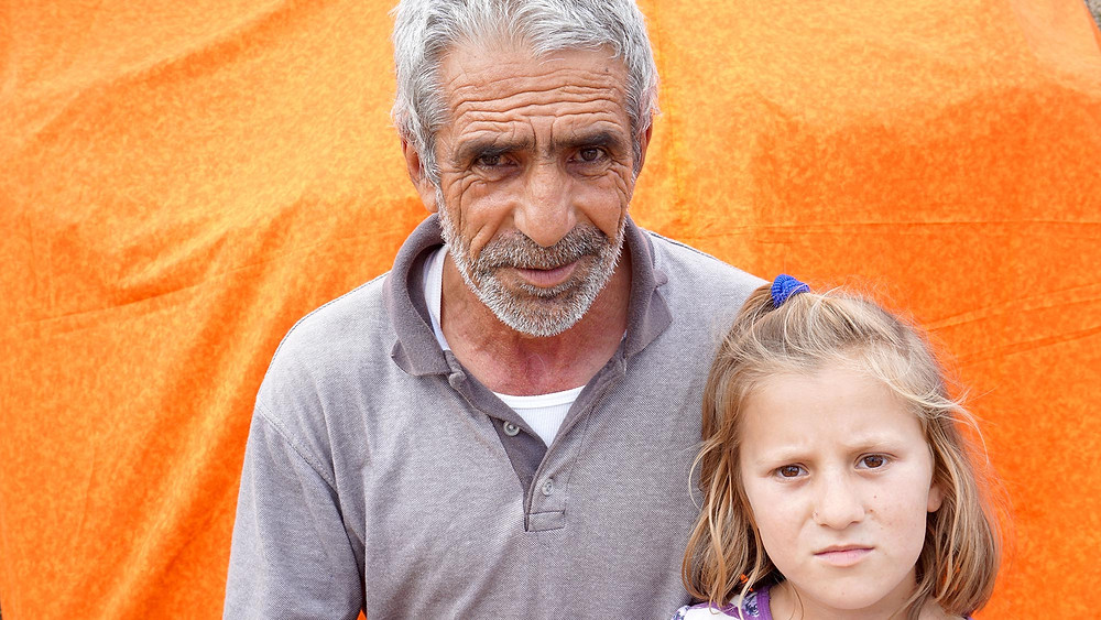A man and his granddaughter detained at the Vial Refugee Camp in Chios, Greece. July 2018. (Photo from The Power of Faces)