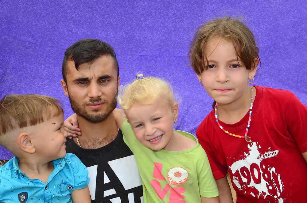 A father poses with his three children outside the Vial Refugee Camp in Chios, Greece. July 2018. (Photo from The Power of Faces)