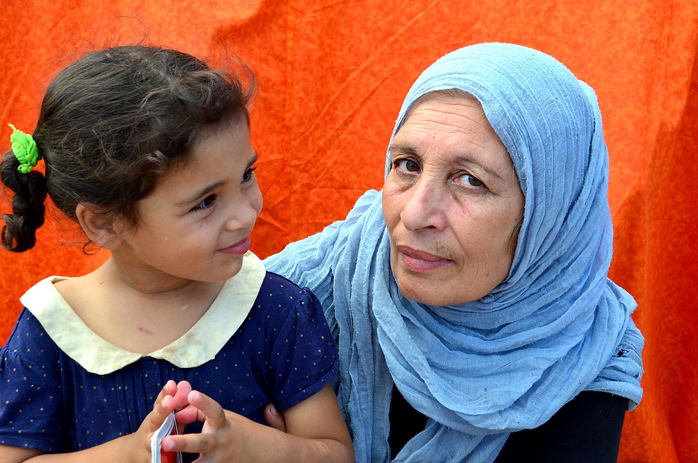 A mother with her daughter outside the Vial Refugee Camp in Chios, Greece with the orange backdrop behind. July 2018. (Photo from The Power of Faces)