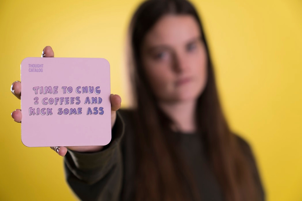 Girl holding up a quote card. Blog on Positivity by Cheltennham Lifestyle and Business.