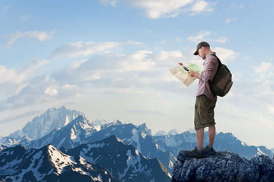 Man standing on mountain with map
