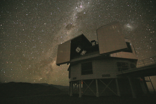 Nighttime picture of Magellen telescope in front of a nighttime sky full of stars.