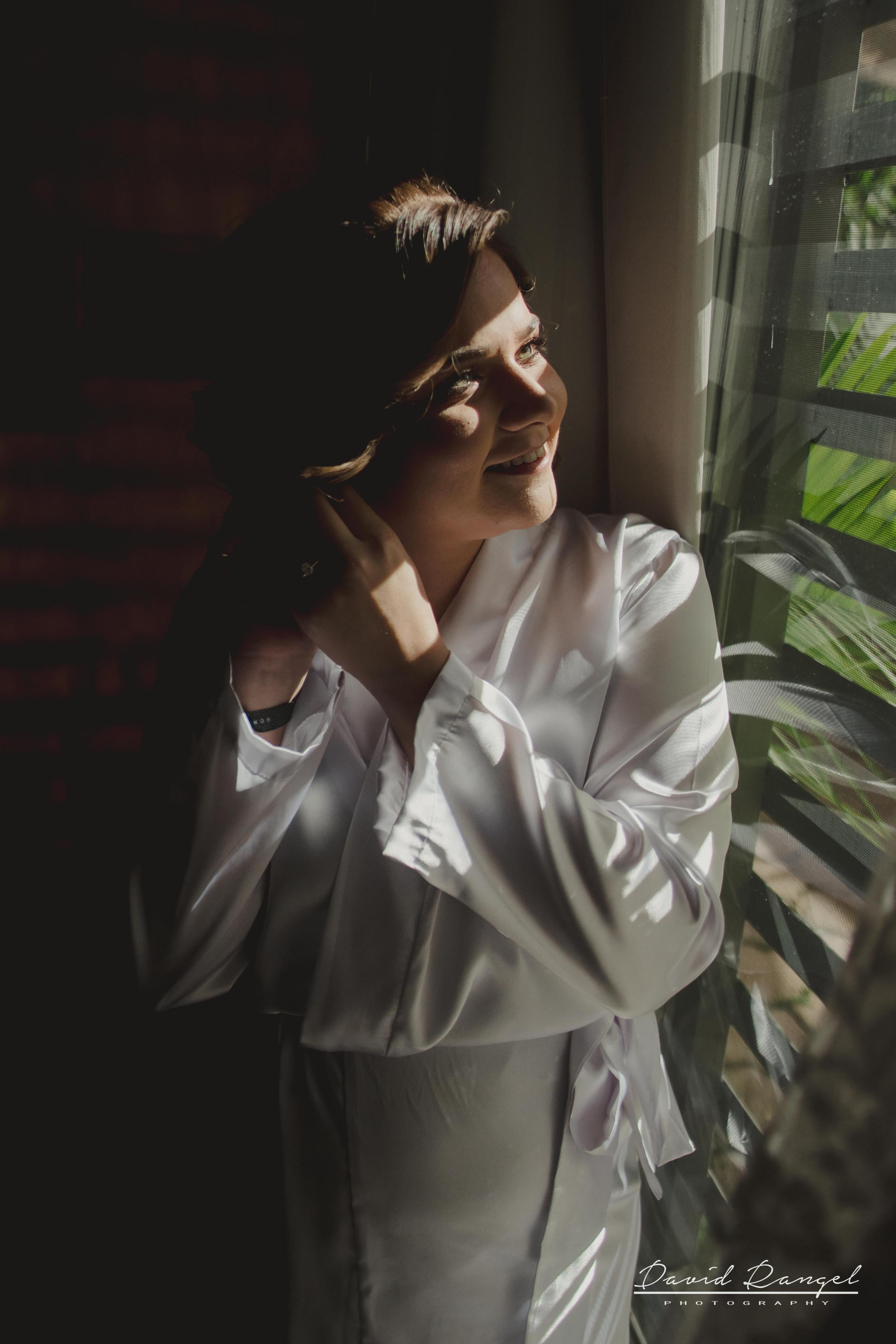 bride+getting+ready+shadow+earring++bathrobe+natural+ligh+photo+destination+wedding+isla+blanca+smile