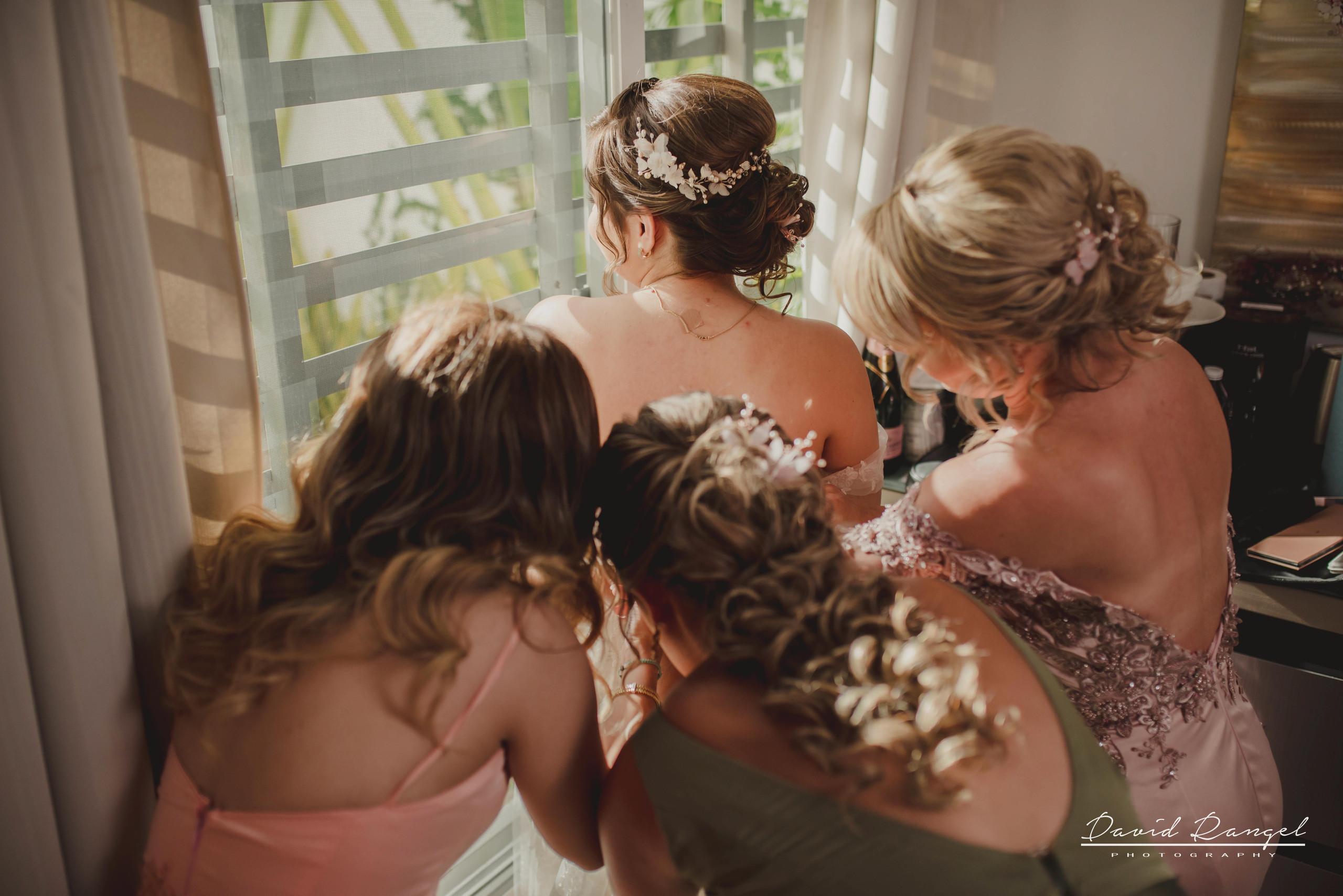 bride+getting+ready+shadow+earring++bathrobe+natural+ligh+photo+destination+wedding+isla+blanca+smile+mirror+photo+celebration+bridesmaids+mother+sister+bestfriend+closing+dress