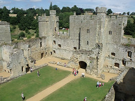 Sunny day at Bodiam Castle showing the repaired external walls and crumbling interior stonework