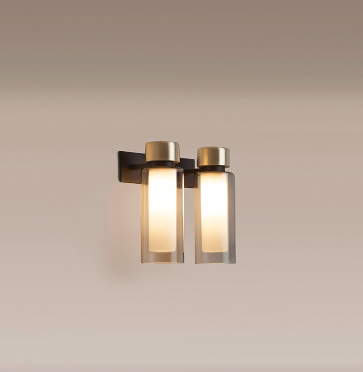 Smoked double wall glass wall lamp with brushed brass details and steel structure