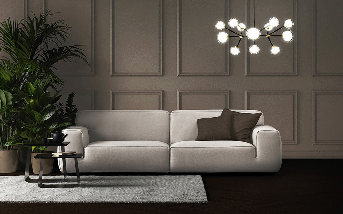 Beige linen upholstered sofa. Sphere shaped double wall glass diffusers chandelier with black powder coated steel structure and brass details. Blue steel coffee tables with dark brown lacquered MDF top