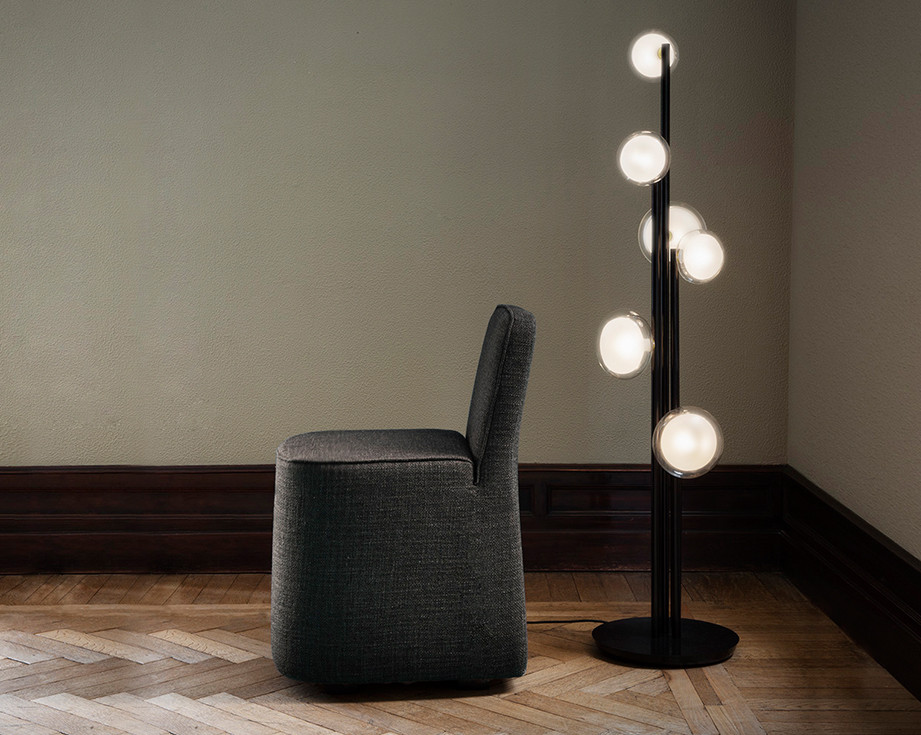 Linen upholstered monolithic chair.Sphere shaped double wall glass diffusers floor lamp with black powder coated steel structure and brass details