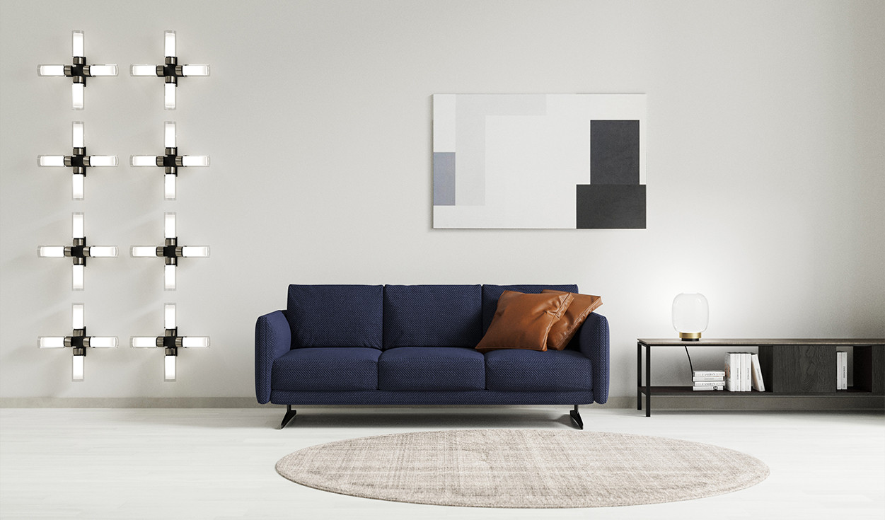 Fabric upholdtered sofa with black nickel steel feet. Metal frame wood sideboard with ceramic top and shelf. Transparent Murano glass diffuser table lamp with polished brass rim detail. Double wall glass cross shaped wall lamp