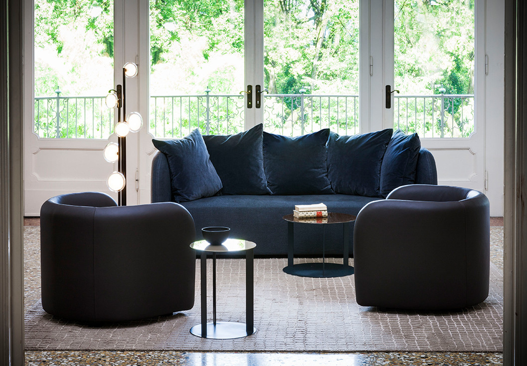 Brown leather upholstered armchairs. Fabric upholstered sofa with blue velvet cushions. Blue steel coffee tables with colored glass tops. Sphere shaped double wall glass diffusers floor lamp with black powder coated steel structure and brass details