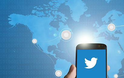 Mean Tweets image - a blue map in the background with a hand holding a cell phone in the bottom left foreground. the cell phone shows a twitter logo.