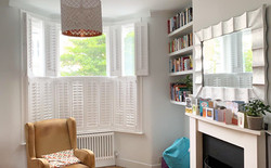 white tier-on-tier living room bay shutters