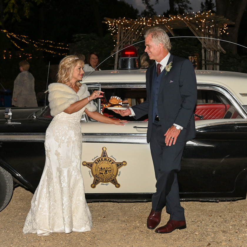 Bride and Groom pose with vintage sheriffs car