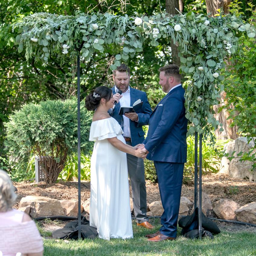 Exchanging vows at small backyard wedding