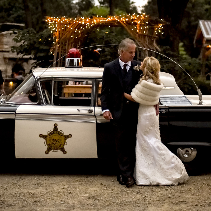 Bride and Groom in front of vintage Sheriff Car