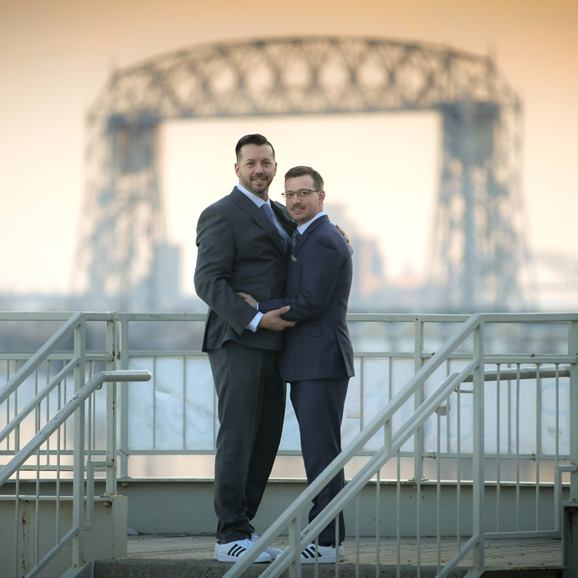 Grooms embrace near water