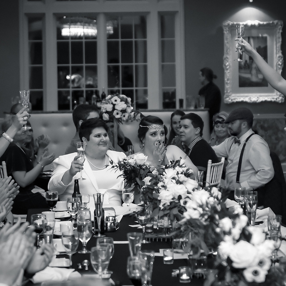 Black & White photography of wedding couple during a toast