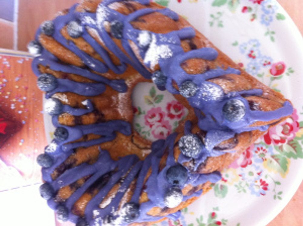 Lavender coloured glace icing, topped with more blueberries and icing sugar dusted on top.