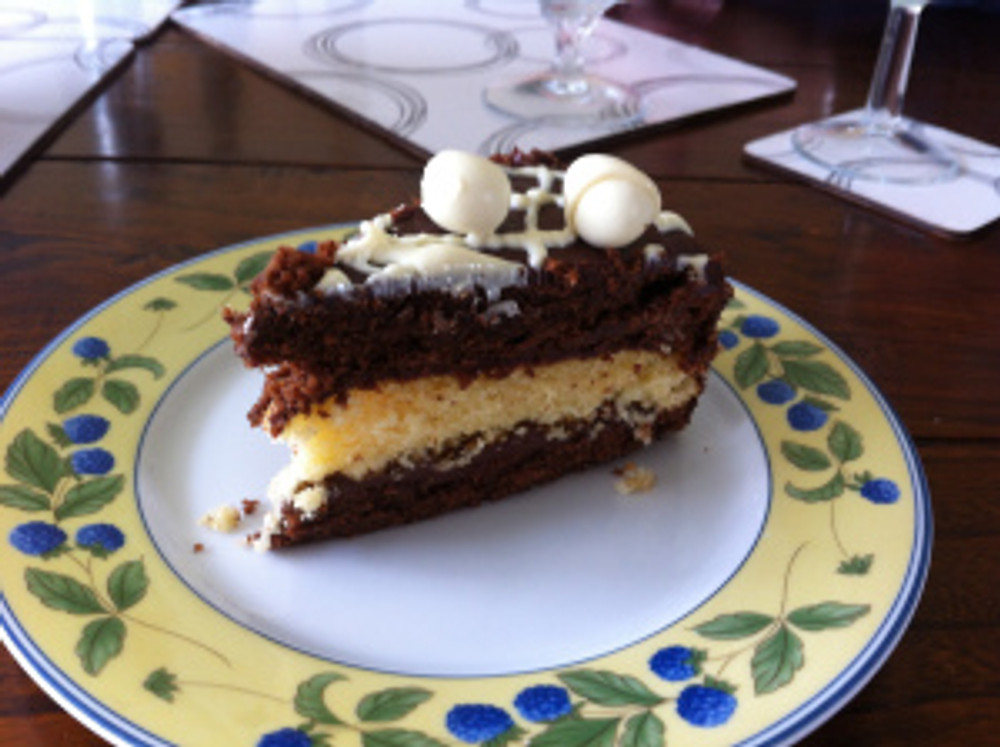 Showing a slice of cake cut up.  The layer of white chocolate is in the middle with the dark chocolate cake either side of it.