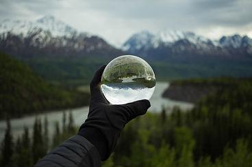 Hand mit Kristallkugel vor Fluss und Ber