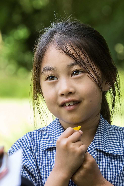 child in school outside with flower in uniform
