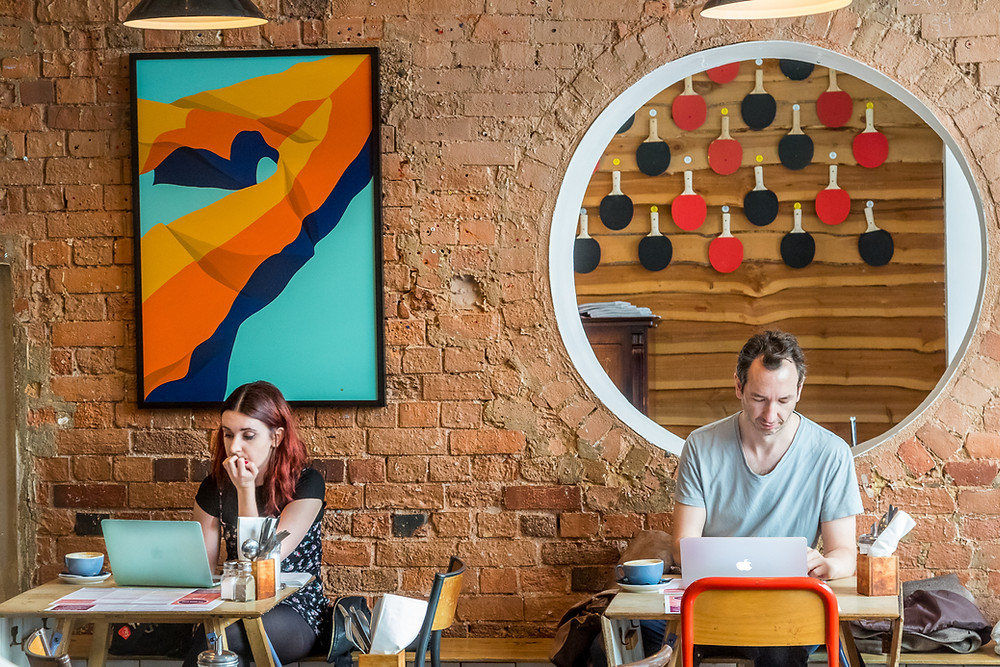How to Start a Photography Side Hustle freelancers in a shoreditch cafe