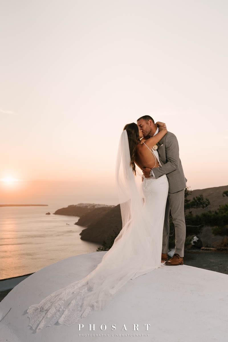 bride and groom kiss on wedding day in santorini