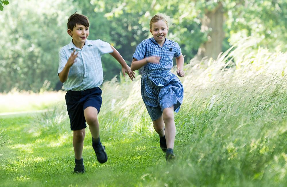 children running through park in photograph
