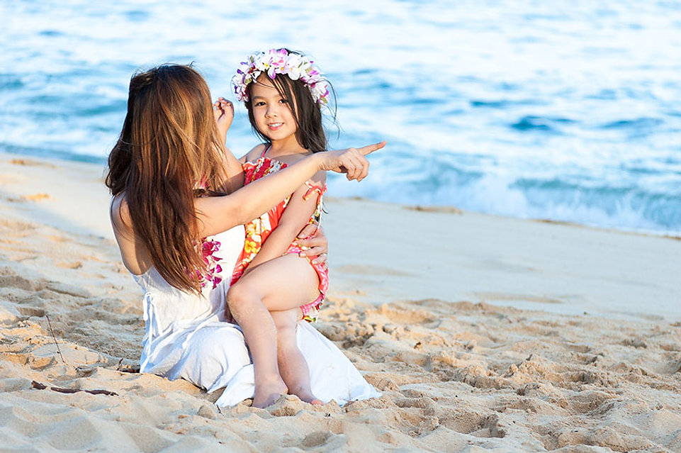 Mother & daughter in floral dresses on the beach.