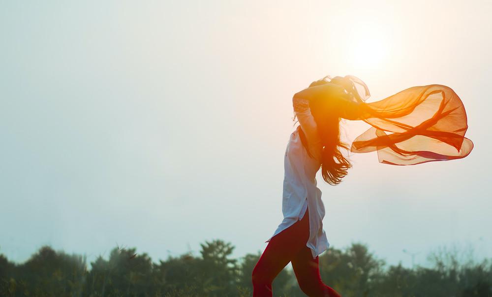 mulher feliz no jardim com um lenço esvoaçante na mão
