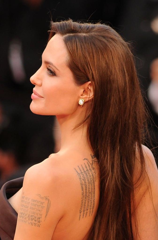 Angelina Jolie com vestido tomara de caia marrom e cabelo solto e longo mostrando suas tatuagens nas costas e braços