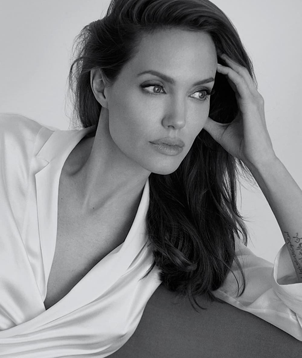 Angelina Jolie em look de camisa branca em foto preta e branco apoiando a cabeça em uma das mãos e olhando para o horizonte