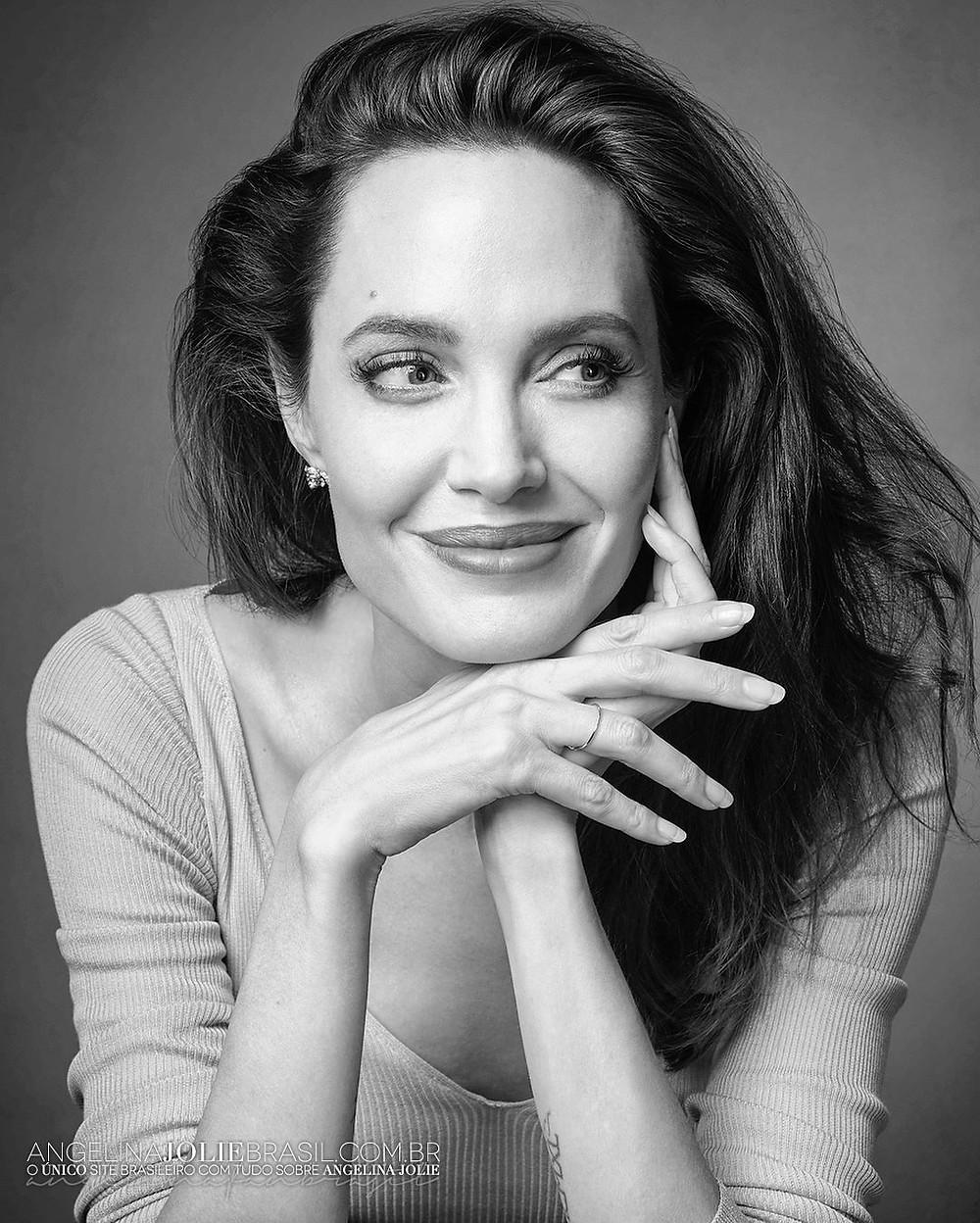 Angelina Jolie em foto preta e branca apoiando o queixo em uma das mãos