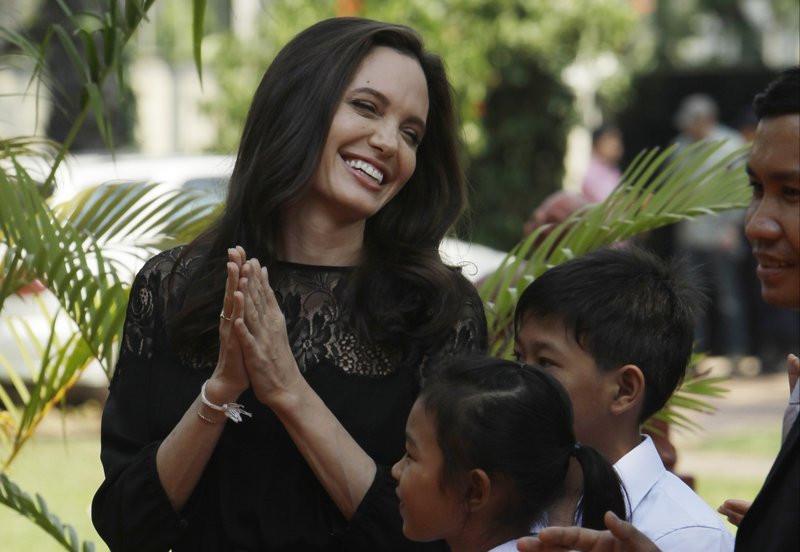 Angelina Jolie de mãos dadas e sorrindo ao redor de crianças no Cambodia