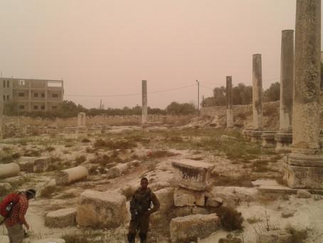 Israeli soldier among ancient Jewish ruins in a modern Arab village