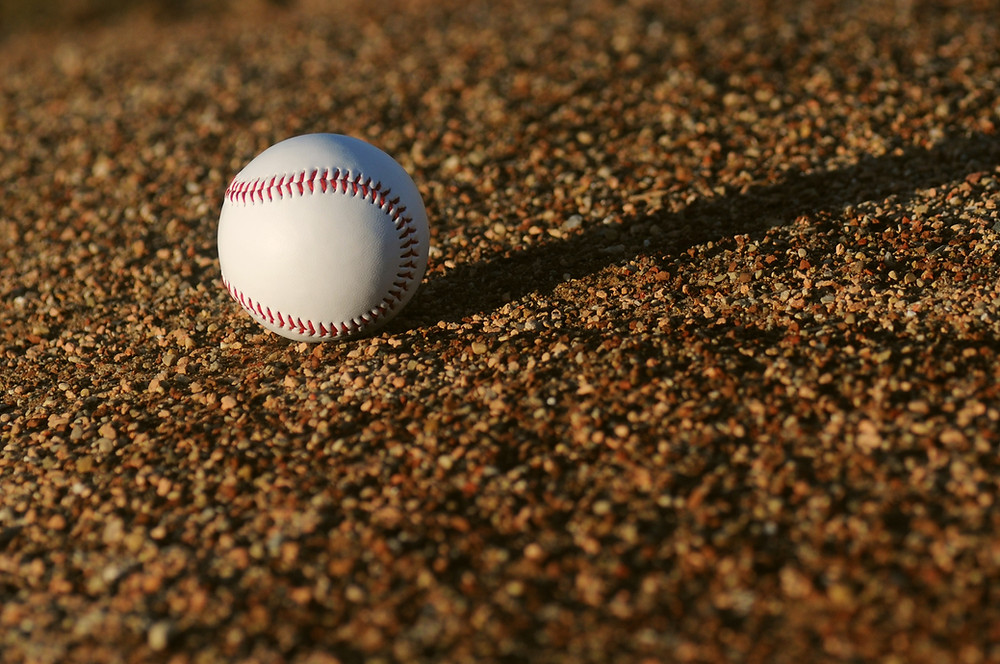 Image of a baseball on the dirt of a baseball field