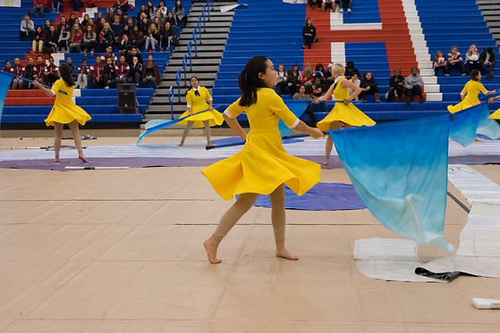 MVHS Winter Guard in yellow dresses with blue flags during a competition/performance.