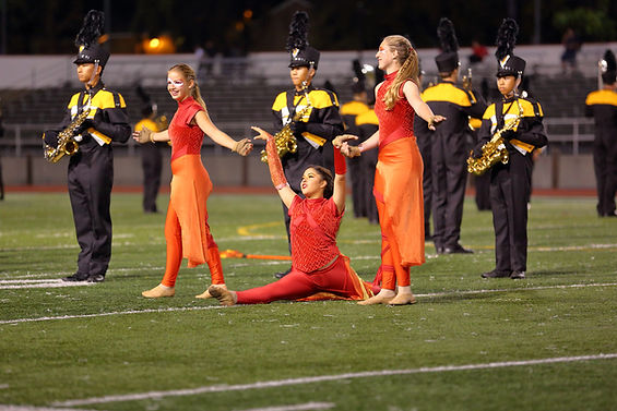 3 Color Guard girls in orange during performance. One is doing a split.