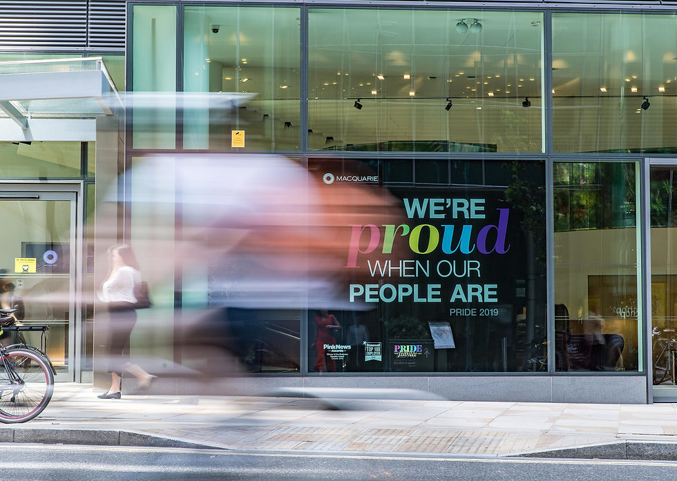 Cyclist riding past PRIDE installation at Ropemaker Place