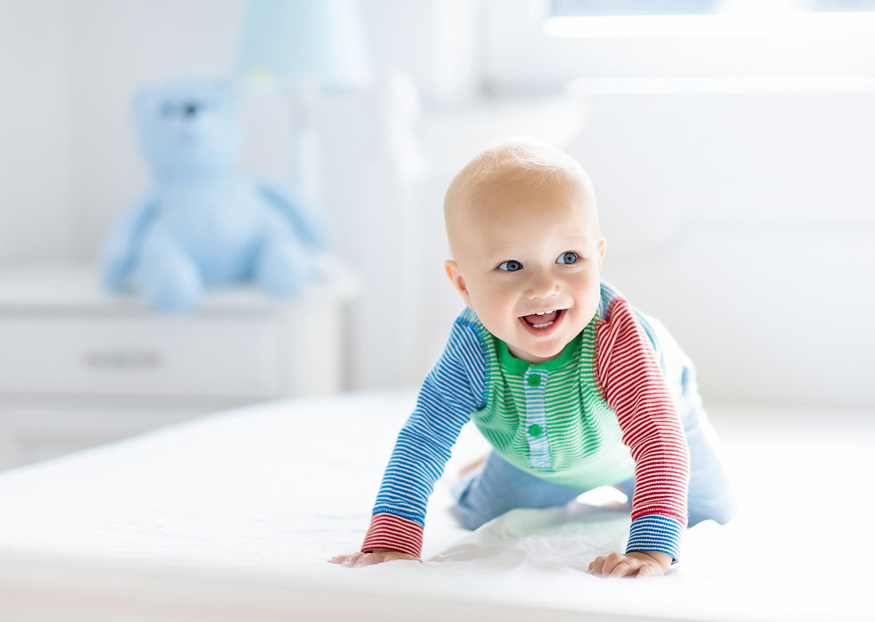 Baby crawing across a bed in a nursery