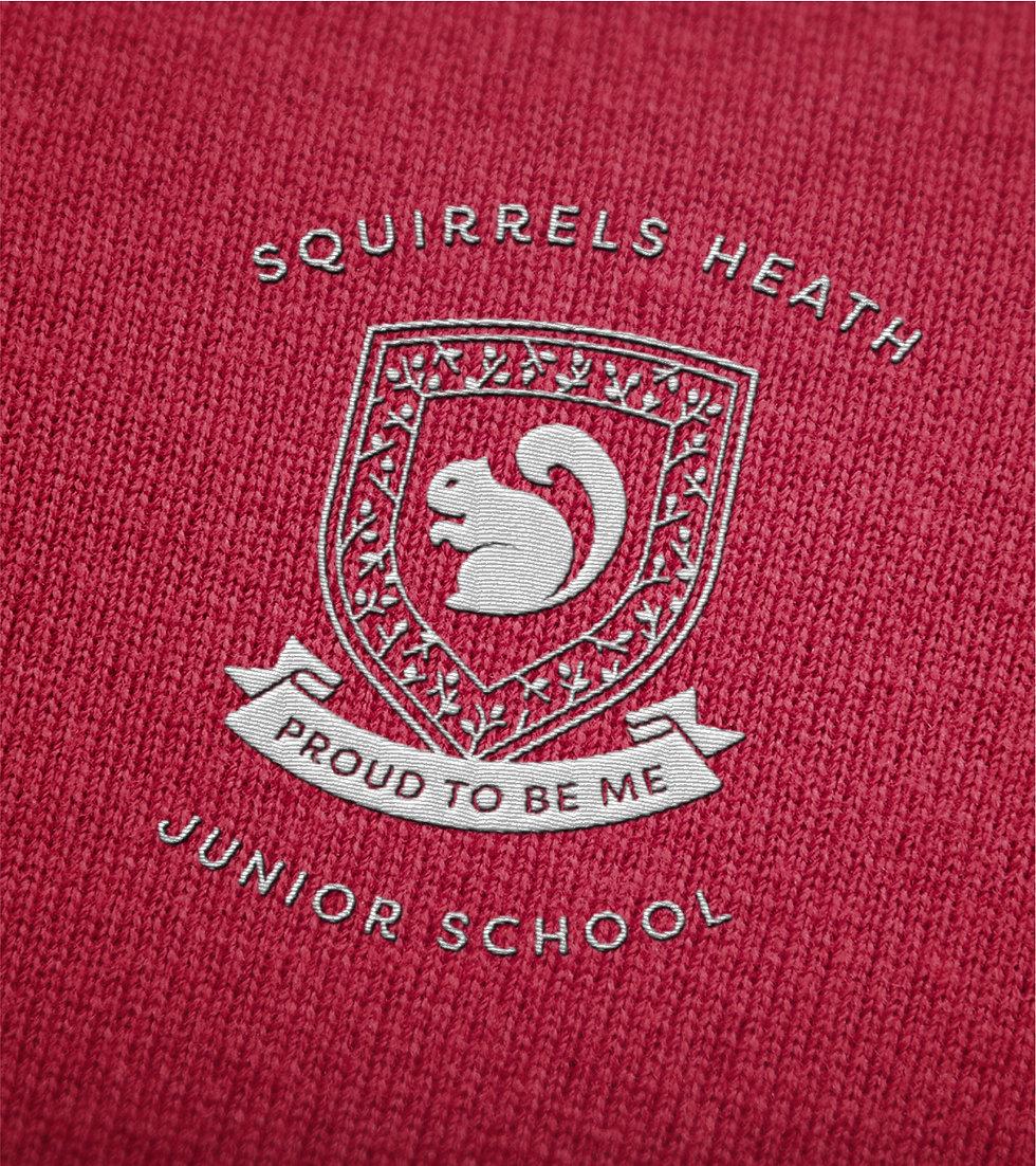 School crest sewn onto red jumper