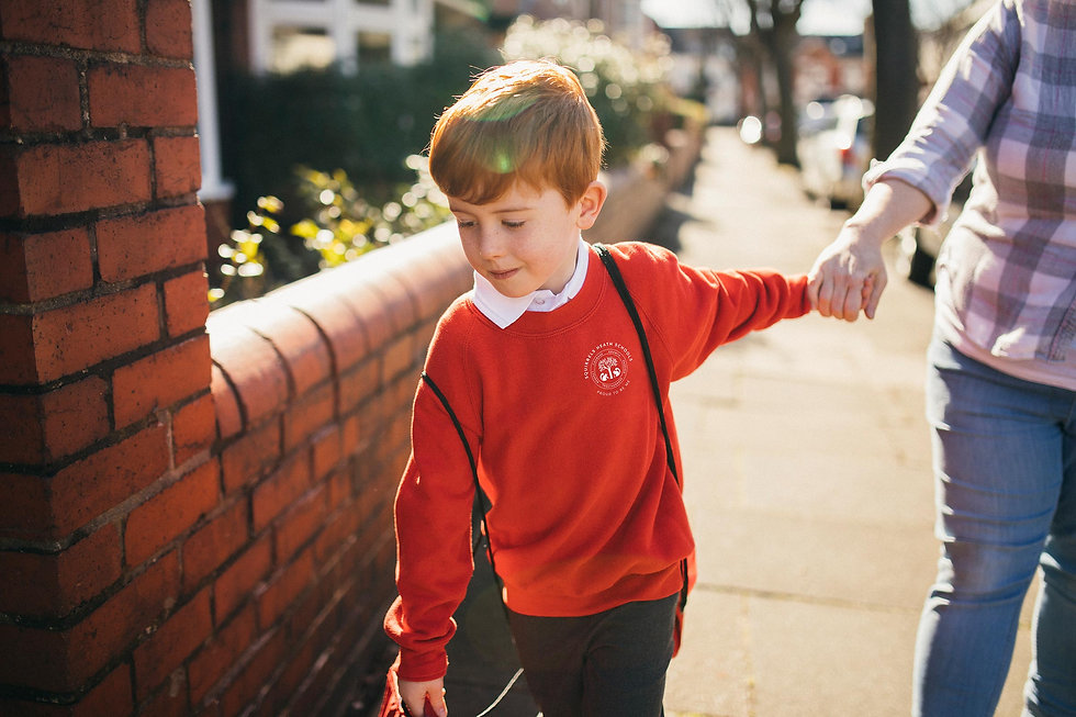 Young boy walking to school with his mum in the new uniform