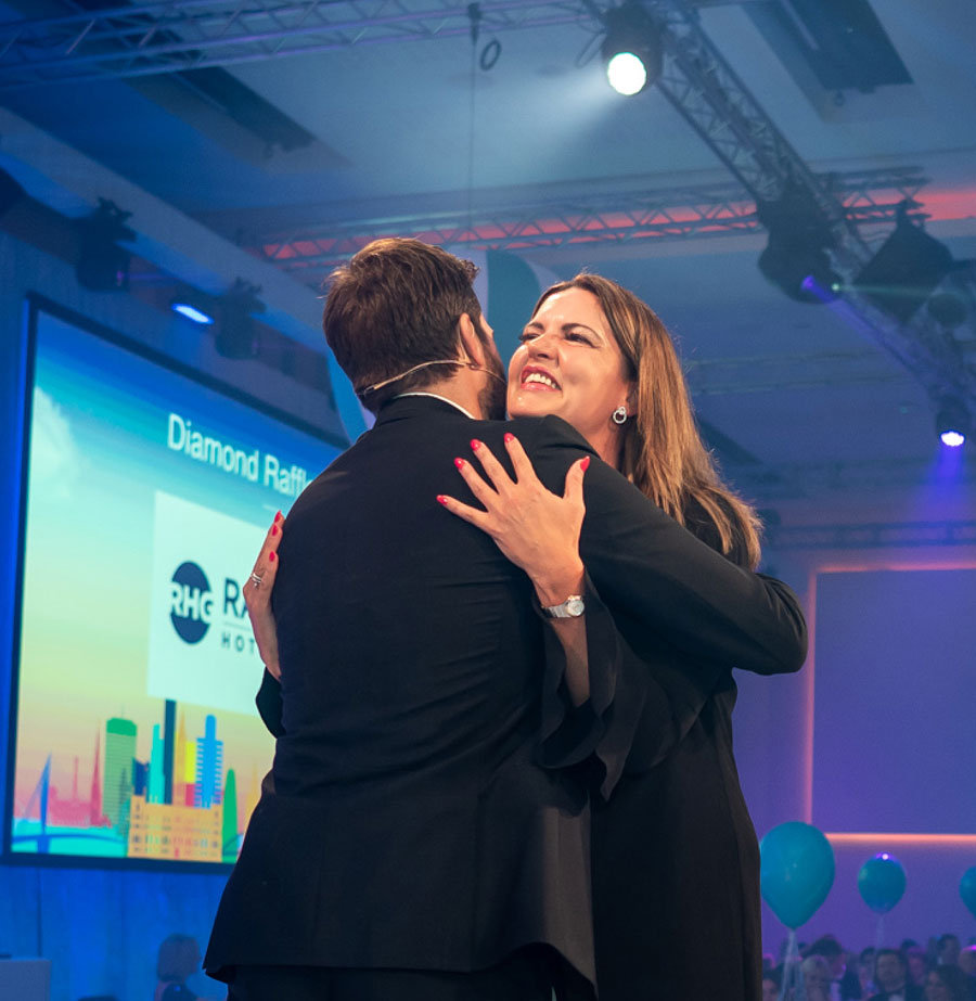 Two event attendees hugging on stage