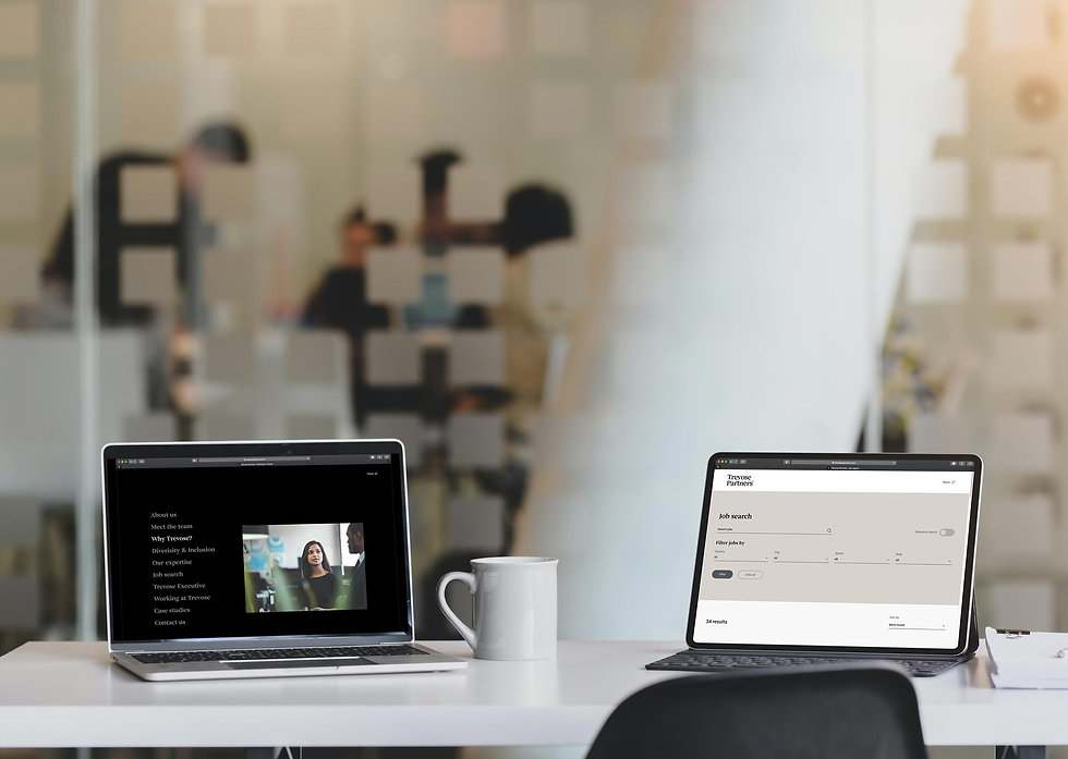 New website displayed on laptop and tablet side-by-side on an office desk