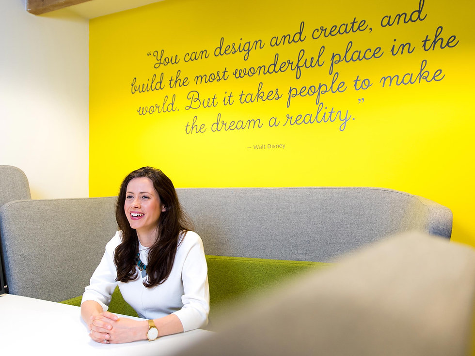 ExCeL team member in front of branded wall art featuring a quote from Walt Disney