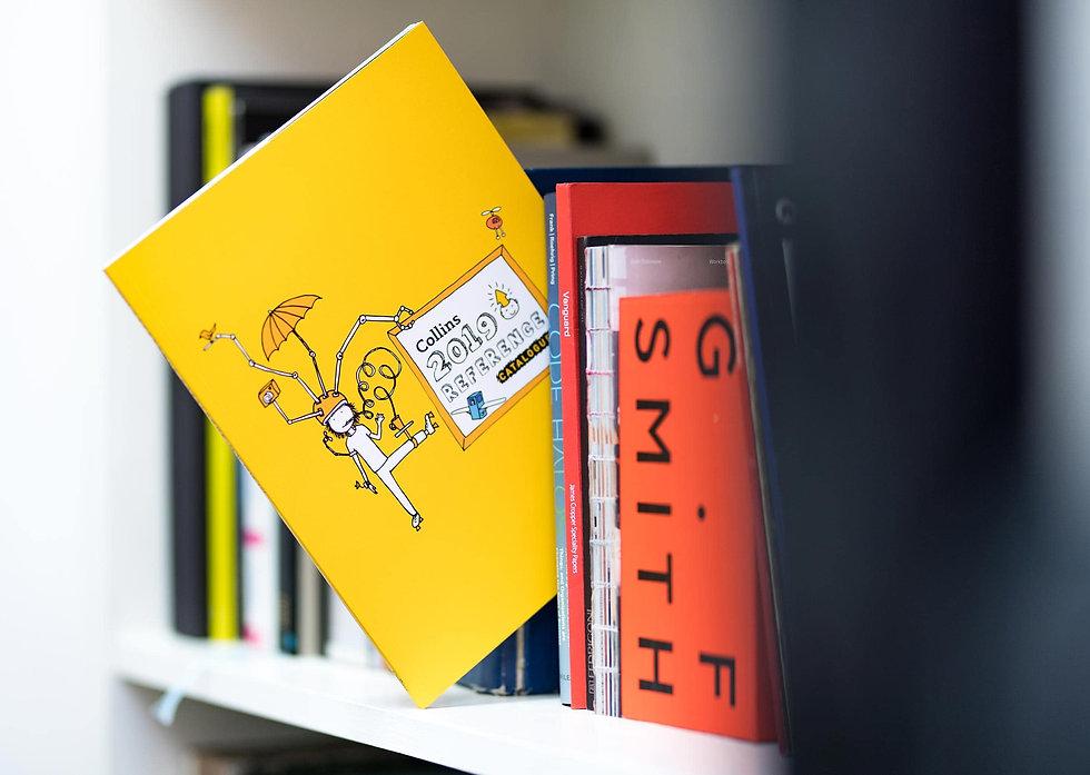 Catalogue cover poking out of a bookshelf