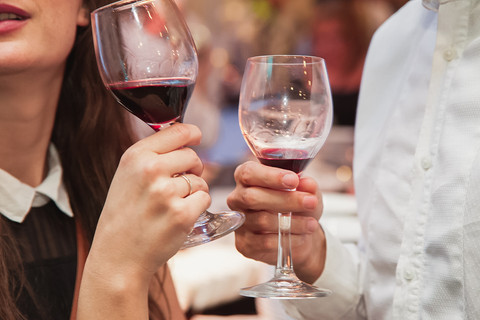 Hands holding red wine at Stellenbosch at Summerplace event