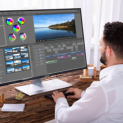 An editor splicing videos clips with editing software