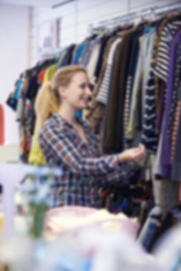 Female Shopper In Thrift Store Looking A
